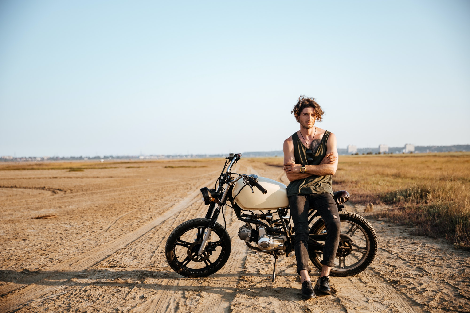 Young brutal man leaning on a motorcycle
